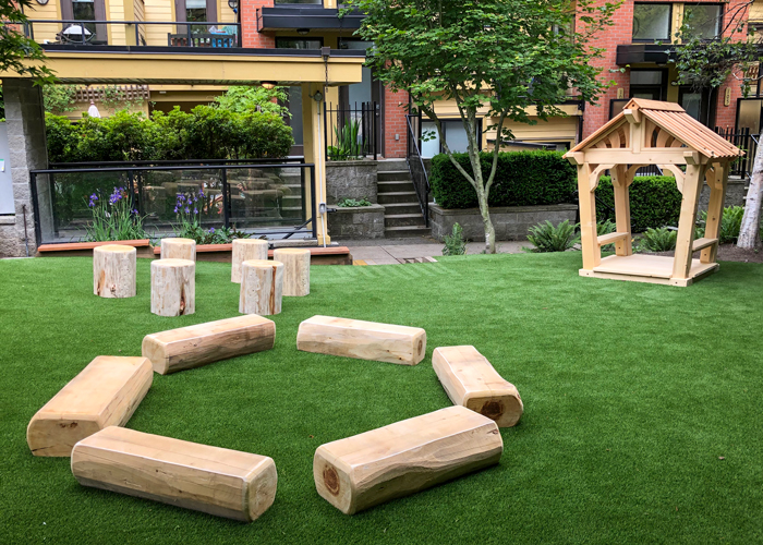 Play area with Log seats, logs circle, and a playhouse
