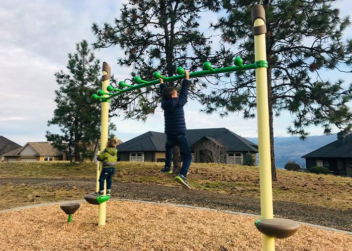 boy swinging on overhead play event