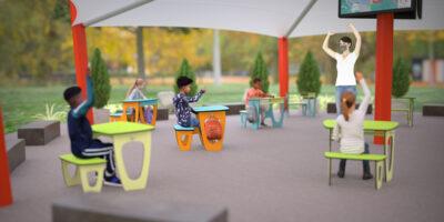 children sitting in desks outdoors