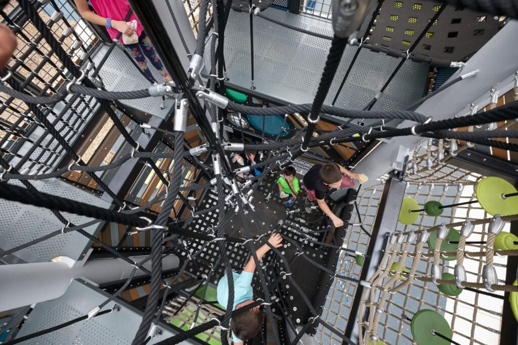 risky play showing kids climbing through a maze of nets inside a playground tower