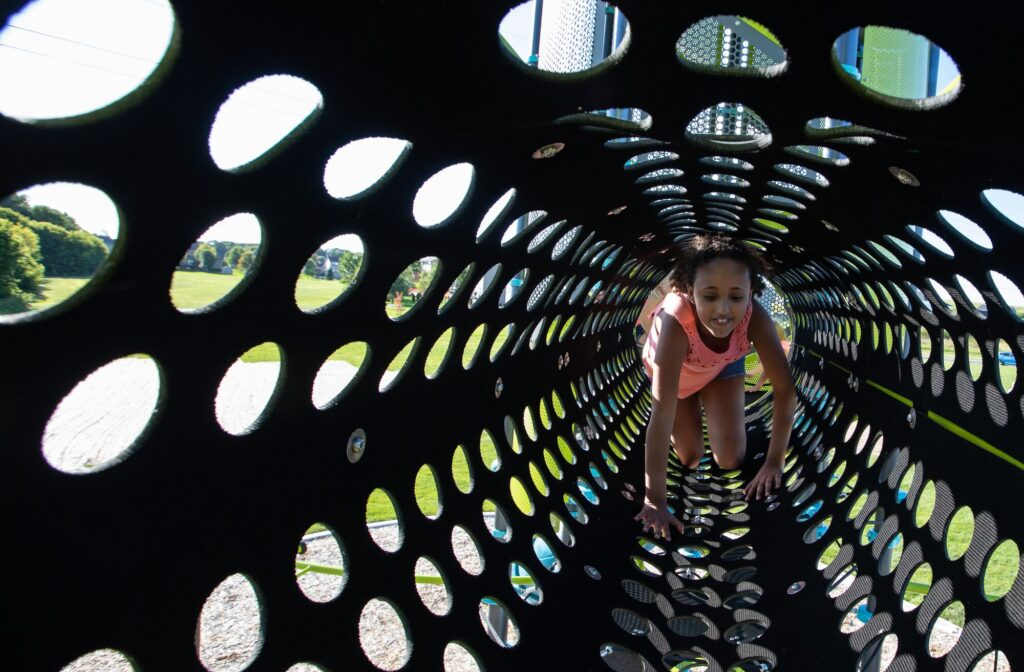 risky play showing a girl crawling through high tunnel