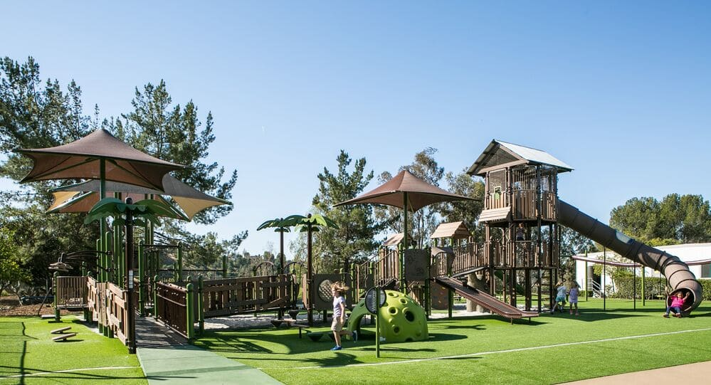 Inclusive Playground Design featuring a natural look and artificial grass surfacing.