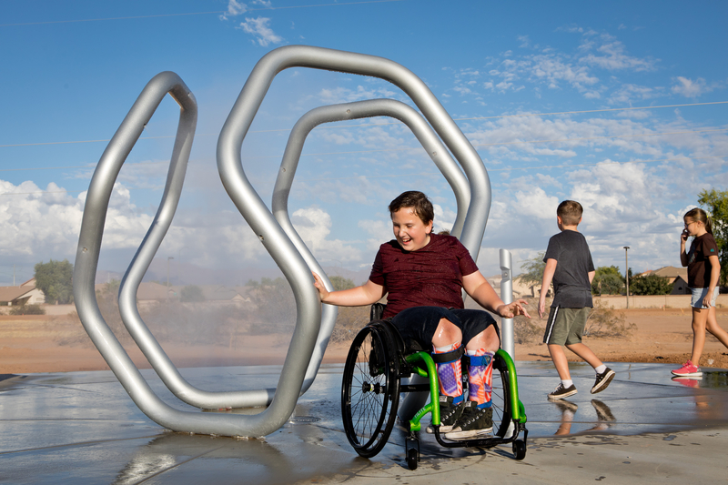 Boy in wheelchair getting misted in a waterpark